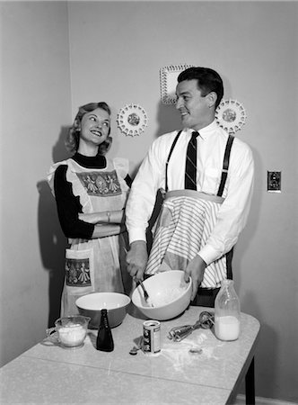 simsearch:846-02793283,k - 1950s COUPLE HUSBAND WIFE KITCHEN TABLE BOTH WEAR APRON MAN MIXING SPOON BOWL BLENDING INGREDIENTS WOMAN ARMS FOLDED SMILING UP AT MAN SATISFIED AMUSED Stock Photo - Rights-Managed, Code: 846-02793184