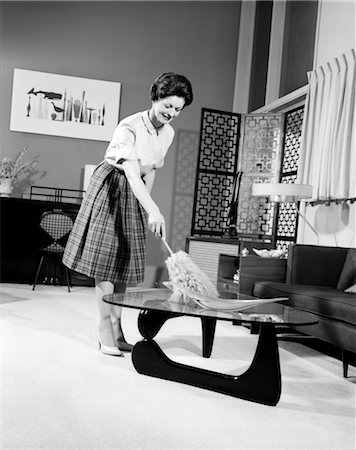 simsearch:846-02793283,k - 1950s WOMAN WEARING A WHITE BLOUSE & PLAID SKIRT DUSTING WITH A FEATHER DUSTER A GLASS TOP COFFEE TABLE Stock Photo - Rights-Managed, Code: 846-02793182