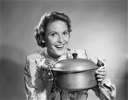 1950s HOUSEWIFE WEARING APRON PROUDLY HOLDING UP A COOKING POT Stock Photo - Rights-Managed, Code: 846-02793196