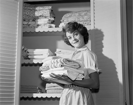 1950s 1960s SMILING WOMAN ABOUT TO PUT FRESH LINENS TOWELS LAUNDRY INTO LINEN CLOSET Stock Photo - Rights-Managed, Code: 846-02793204