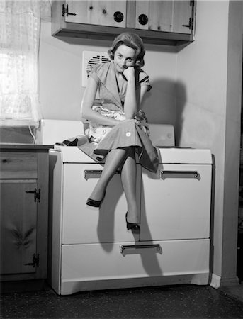 1950s 1960s WOMAN HOUSEWIFE SITTING ATOP ON STOVE ANGRY FRUSTRATED SERIOUS FACIAL EXPRESSION Stock Photo - Rights-Managed, Code: 846-02793203