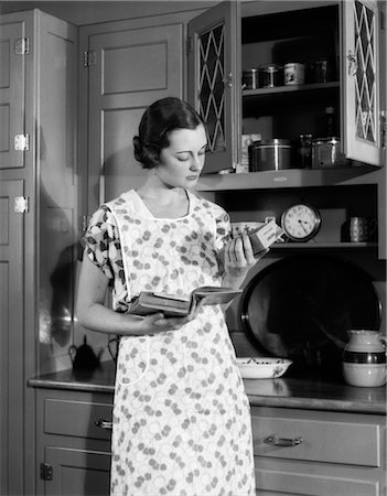 1920s 1930s WOMAN HOUSEWIFE WEARING APRON IN KITCHEN HOLDING COOKBOOK READING PACKAGE OF CORN STARCH Stock Photo - Rights-Managed, Code: 846-02793227
