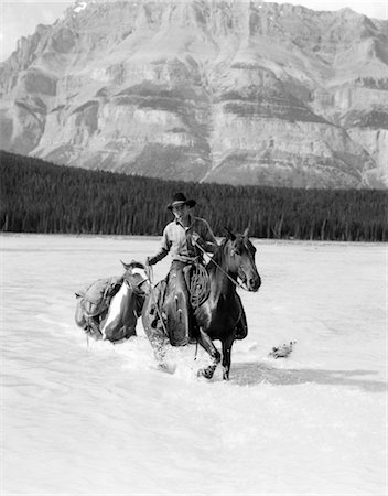 1930s COWBOY WITH BATWING CHAPS ON A BAY HORSE CROSSING A RIVER LEADING A PAINT PACK HORSE WITH MOUNTAINS IN BACKGROUND Stock Photo - Rights-Managed, Code: 846-02793220