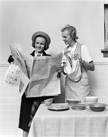 1940s 2 WOMEN IN KITCHEN ONE DRYING DISHES WITH TOWEL OTHER IN HAT COAT HOLDING READING NEWSPAPER Stock Photo - Rights-Managed, Code: 846-02793239