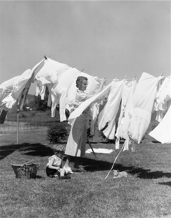 1930s WOMAN IN WHITE COTTON DRESS HANGING A FULL LINE OF CLOTHES IN THE BREEZE WITH A LITTLE BOY & CAT AT HER FEET Stock Photo - Rights-Managed, Code: 846-02793233