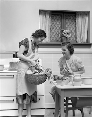 1920s 1930s TWO WOMEN AT KITCHEN TABLE WITH A BASKET OF VEGETABLES ASPARAGUS STOVE Stock Photo - Rights-Managed, Code: 846-02793248