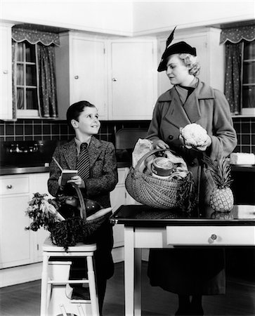 1930s MOTHER & SON IN KITCHEN WITH BASKETS OF GROCERIES CHECKING OFF LIST Stock Photo - Rights-Managed, Code: 846-02793241