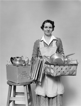 1930s 1940s WOMAN HOUSEWIFE FACING CAMERA HOLDING BASKET FILLED WITH POTS PANS COOKWARE CHORE APRON Stock Photo - Rights-Managed, Code: 846-02793242