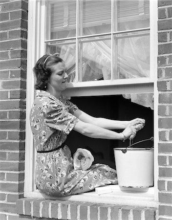 1930s WOMAN SITTING BACKWARDS ON WINDOW LEDGE WASHING WINDOW PANES Stock Photo - Rights-Managed, Code: 846-02793255