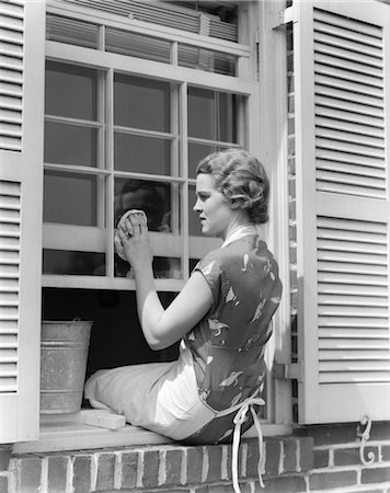 1930s WOMAN IN PRINT DRESS & APRON SITTING ON WINDOWSILL WASHING WINDOW WITH CLOTH AND BUCKET SPRING CLEANING HOUSEWIFE Stock Photo - Rights-Managed, Code: 846-02793258