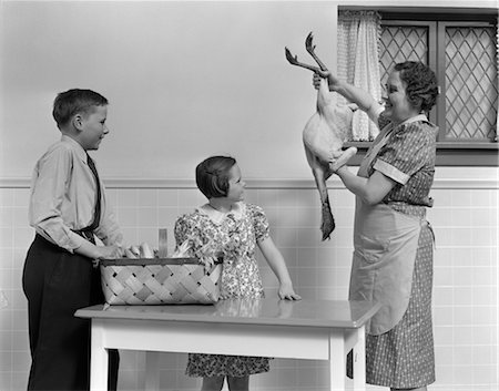 1940s HOUSEWIFE SHOWING RAW FRESH PLUCKED TURKEY TO SON AND DAUGHTER IN KITCHEN Stock Photo - Rights-Managed, Code: 846-02793265