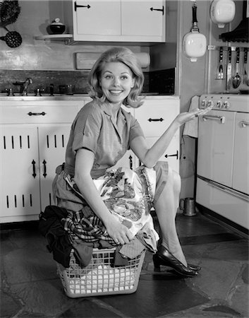 1960s SMILING HOUSEWIFE IN KITCHEN SITTING ON TOP OF FULL LAUNDRY BASKET HOLDING OUT HAND Stock Photo - Rights-Managed, Code: 846-02793278