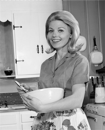 1960s 1970s SMILING BLOND WOMAN HOUSEWIFE IN KITCHEN HOLDING MIXING BOWL AND SPOON Stock Photo - Rights-Managed, Code: 846-02793279