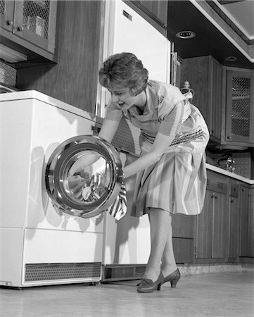 1960s HOUSEWIFE IN KITCHEN PUTTING LAUNDRY INTO WASHER Stock Photo - Rights-Managed, Code: 846-02793270