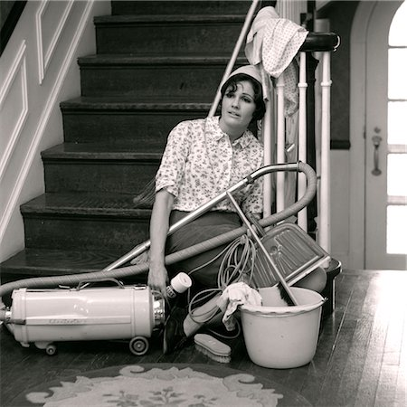1960s 1970s EXHAUSTED-LOOKING HOUSEWIFE SITTING AT FOOT OF STAIRS SURROUNDED BY HOUSE CLEANING TOOLS Stock Photo - Rights-Managed, Code: 846-02793284