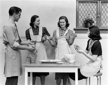 1930s 1940s WOMEN 1 MAN APRONS IN KITCHEN PULLING TAFFY Stock Photo - Rights-Managed, Code: 846-02793283