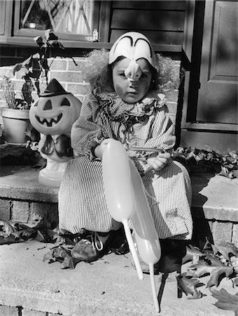 1970s CHILD IN TRICK OR TREAT CLOWN COSTUME SITTING ON FRONT DOOR STEP HOLDING BALLOONS Stock Photo - Rights-Managed, Code: 846-02793308