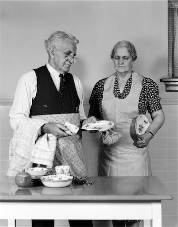 simsearch:846-02793283,k - 1940s 1950s ELDERLY COUPLE MAN WOMAN IN KITCHEN AT TABLE HOLDING DISHES BOTH WEAR APRON EYE GLASSES Stock Photo - Rights-Managed, Code: 846-02793311