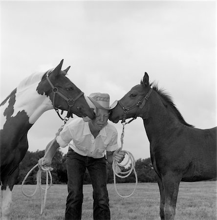 BOY COWBOY WEAR HAT HOLDING ROPES REINS HARNESS HALTER OF 2 HORSES ONE ON EITHER SIDE OF HIS FACE KISSING HIM FUNNY Stock Photo - Rights-Managed, Code: 846-02793326