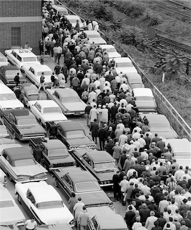 1960s OVERHEAD OF FACTORY WORKERS IN CROWDED PARKING LOT GETTING OUT OF CARS & WALKING TOWARD BUILDING TO WORK Stock Photo - Rights-Managed, Code: 846-02793400