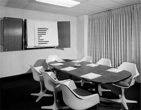 1960s EMPTY CONFERENCE ROOM LONG OVAL TABLE 7 WHITE CHAIRS & CHART POSTED ON THE WALL Stock Photo - Rights-Managed, Code: 846-02793415