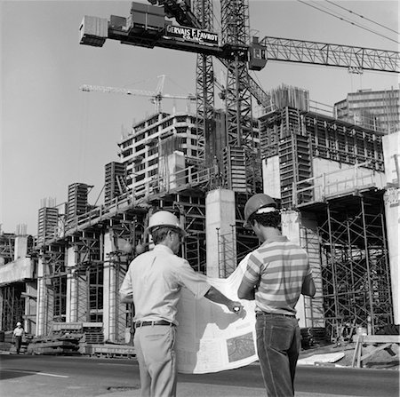 1980s REAR VIEW OF TWO HARD HAT WORKERS STANDING IN FRONT OF MAJOR CONSTRUCTION SITE LOOKING OVER BUILDING PLANS MEN OUTDOOR Stock Photo - Rights-Managed, Code: 846-02793439