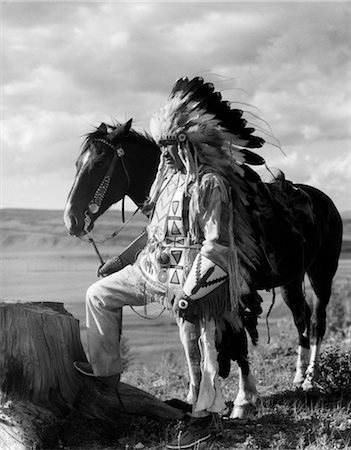 1930s PORTRAIT SIOUX INDIAN MAN WEARING FEATHER HEADDRESS HOLDING REINS OF HORSE Stock Photo - Rights-Managed, Code: 846-02793445