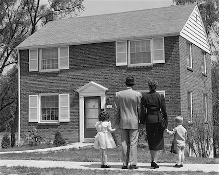 1950s BACK VIEW OF FAMILY OF 4 STANDING IN FRONT OF NEW HOME HOLDING HANDS Stock Photo - Rights-Managed, Code: 846-02793450
