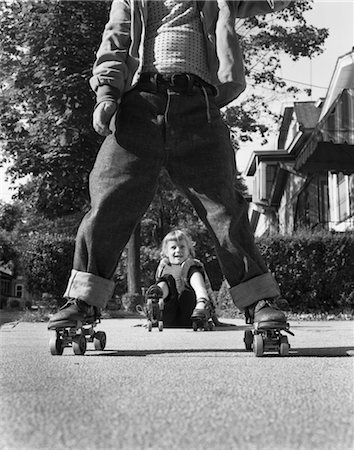 1950s LITTLE BOY AND GIRL PLAYING ON SIDEWALK WEARING METAL ROLLER SKATES AND BLUE JEANS GIRL HAS FALLEN ON HER BUTT Stock Photo - Rights-Managed, Code: 846-02793537