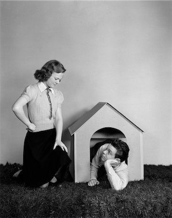 1940s YOUNG TEEN COUPLE ARGUMENT GIRL FROWNING BOY LYING IN DOGHOUSE DOG HOUSE Stock Photo - Rights-Managed, Code: 846-02793533