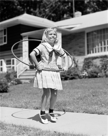 1950s GIRL IN DRESS ON SUBURBAN SIDEWALK USING THE HULA HOOP Stock Photo - Rights-Managed, Code: 846-02793552