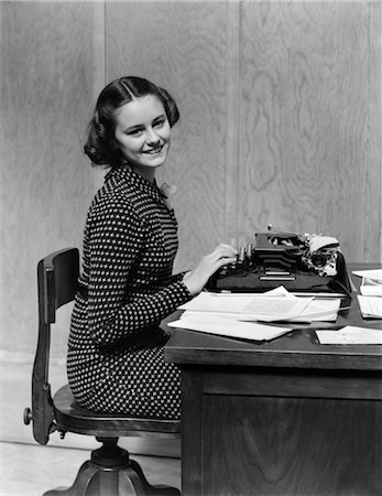 secretary desk - 1940s YOUNG WOMAN OFFICE SECRETARY SMILING SITTING AT DESK USING MANUAL TYPEWRITER LOOKING AT CAMERA Stock Photo - Rights-Managed, Code: 846-02793571