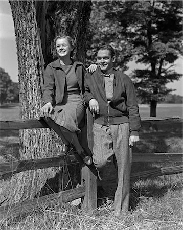 1940s TEEN COUPLE BOY GIRL HAPPY SMILING FULL LENGTH PORTRAIT BY WOODEN FENCE AND TREE Stock Photo - Rights-Managed, Code: 846-02793596