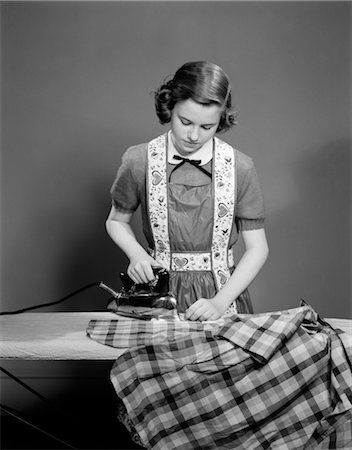 1950s YOUNG TEEN GIRL WEARING APRON IRONING SHIRT HOUSEHOLD CHORE Stock Photo - Rights-Managed, Code: 846-02793604