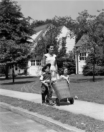 1950s MOM ON SIDEWALK PUSHING WICKER SHOPPING BASKET WITH DAUGHTER AND SON IN COWBOY HAT WALKING BESIDE HER Stock Photo - Rights-Managed, Code: 846-02793629