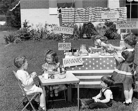 1950s KIDS IN BACKYARD PLAYING STORE WITH SIGNS SELLING APPLES BANANAS SANDWICHES LOLLYPOPS Stock Photo - Rights-Managed, Code: 846-02793641