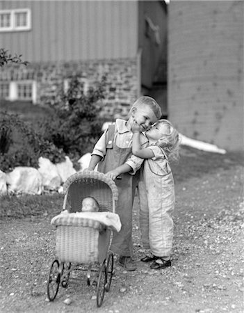 1930s 1940s LITTLE GIRL KISSING BOY PUSHING TOY BABY CARRIAGE IN FRONT OF BARN Stock Photo - Rights-Managed, Code: 846-02793643