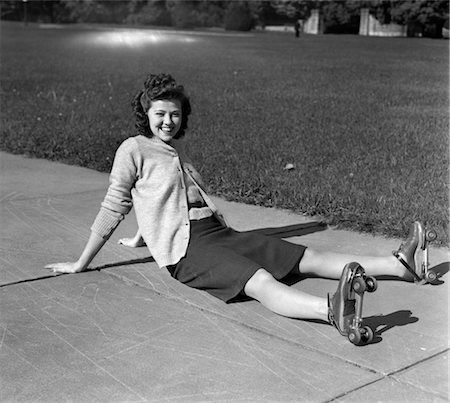 1940s LAUGHING YOUNG WOMAN TEEN GIRL SITTING ON SIDEWALK HAVING FALLEN DOWN ON ROLLER SKATES Stock Photo - Rights-Managed, Code: 846-02793705