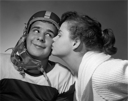 1950s TEEN GIRL PONY TAIL KISSING BOY WEARING FOOTBALL HELMET ON THE CHEEK Stock Photo - Rights-Managed, Code: 846-02793711