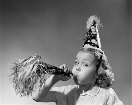 1950s GIRL WEARING PARTY HAT BLOWING INTO NOISE MAKER Stock Photo - Rights-Managed, Code: 846-02793721