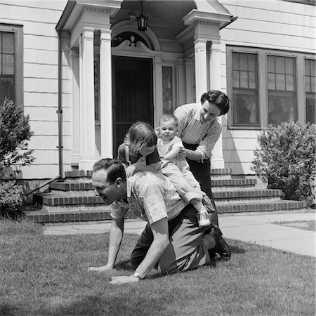 1950s FAMILY FRONT LAWN HOUSE TWO KIDS RIDING FATHER PIGGYBACK MOTHER HELPING TODDLER BABY Stock Photo - Rights-Managed, Code: 846-02793781
