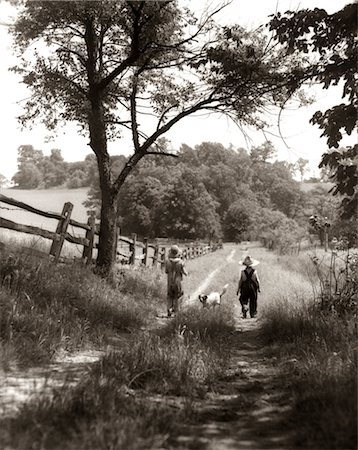 1930s REAR VIEW OF BOY & GIRL IN STRAW HATS & OVERALLS WALKING DOWN FARM ROAD WITH DOG BETWEEN THEM Stock Photo - Rights-Managed, Code: 846-02793805