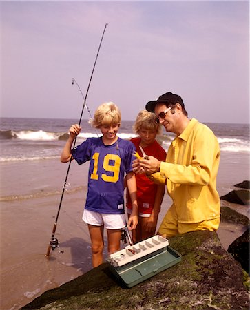 1970s MAN FATHER TEACHING 2 BOYS SONS FISHING GEAR BEACH SURF OCEAN CITY NEW JERSEY Stock Photo - Rights-Managed, Code: 846-02793896