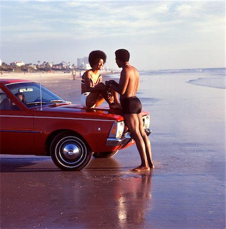 1970s SMILING ROMANTIC AFRICAN AMERICAN VACATION COUPLE AT BEACH WOMAN SITTING ON CAR HOOD MAN HOLDING HANDS Stock Photo - Rights-Managed, Code: 846-02793924