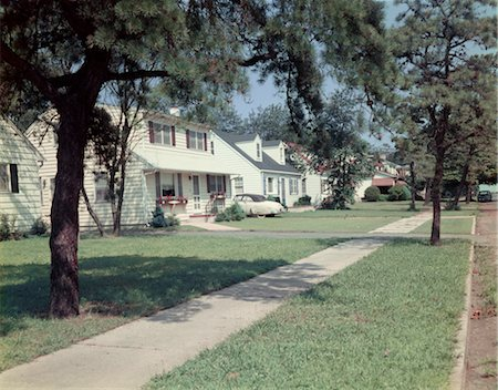 1950s SUBURBAN STREET WHITE HOUSES WITH SIDEWALK RUNNING DOWN MIDDLE OF IMAGE YARD GREEN GRASS SPRING LAKE NJ Stock Photo - Rights-Managed, Code: 846-02793935