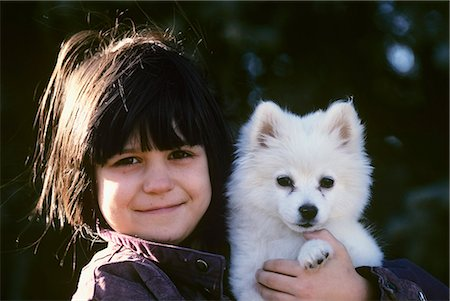 furry - EIGHT-YEAR-OLD GIRL HOLDING WHITE PUPPY AMERICAN ESKIMO SPITZ Stock Photo - Rights-Managed, Code: 846-03164150