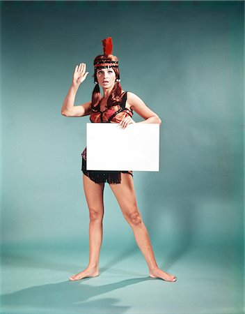 1960s 1970s CHARACTER WOMAN WEARING NATIVE AMERICAN FEATHER HEADDRESS MAKING HOW GESTURE HOLDING BLANK SIGN Stock Photo - Rights-Managed, Code: 846-03164521