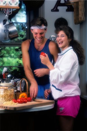 simsearch:846-02793283,k - 1990s LAUGHING YOUNG COUPLE IN KITCHEN CUTTING VEGETABLES FOR SALAD Stock Photo - Rights-Managed, Code: 846-03164578