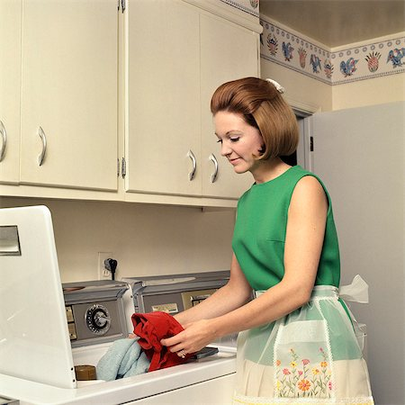 1970s WOMAN HOUSEWIFE HOMEMAKER WEARING APRON LOADING LAUNDRY INTO WASHING MACHINE Stock Photo - Rights-Managed, Code: 846-03164624