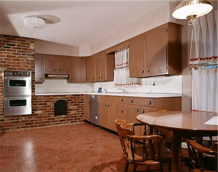 1970s KITCHEN WITH DARK WOODEN CABINETS BRICK WALL AND ...